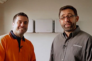 Two men standing in front of Enphase AC batteries installed on wall