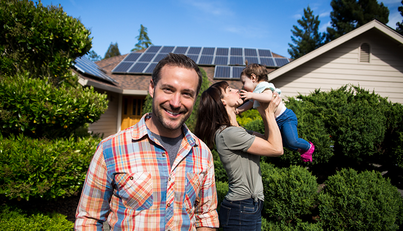 Family in front of house with solar panels on roof