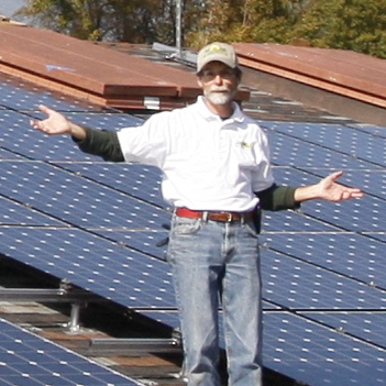 Jim Jenal stands in front of Enphase microinverter system on rooftop