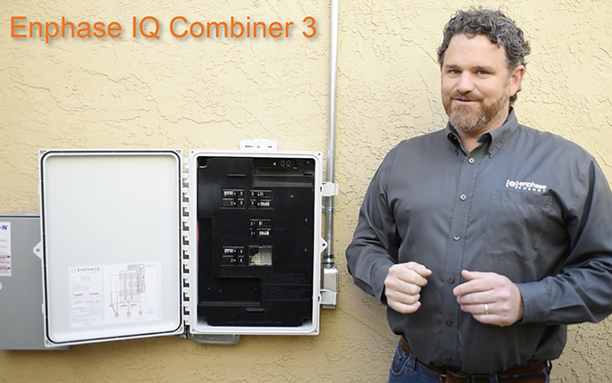 Solar installer standing in front of Enphase IQ Combiner 3 product mounted on a wall
