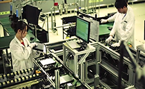 Two lab technicians in the Enphase quality testing lab looking at computer monitors and using testing machinery