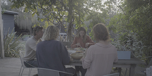 Family sitting at table outside