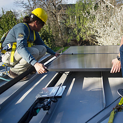 Image of installers connecting solar panel to racking system on roof