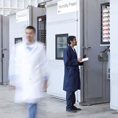 Two lab technicians stand in Enphase microinverter quality testing lab in front of the humidity freezer machine