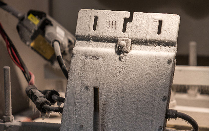 Image of Enphase solar inverter covered in frost and condensation from being tested in Enphase quality lab