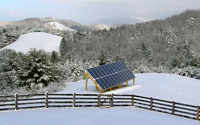 Enphase solar inverter installed on the ground in the Arctic surrounded by snow