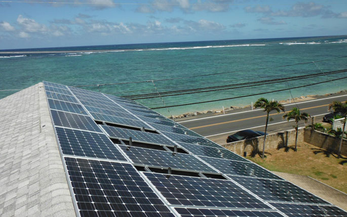 Solar panels and solar power inverters installed on a roof near the beach next to sand and ocean