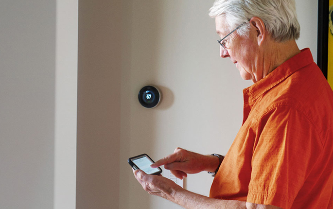 Man using iphone in front of Nest thermostat